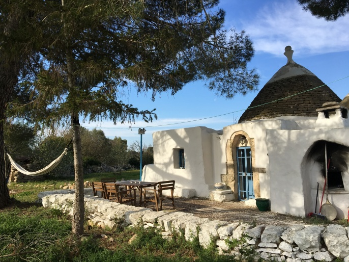 The trullo is shaded by the pine trees